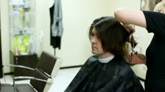 Young man sits in hairdressing salon in seat to make hairdress - stock footage