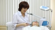 Stock Video Footage of Beautician does galvanotherapy on face to client