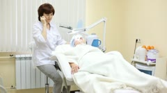 Patient lies in cosmetology armchair and cosmetician speaks by phone - stock footage