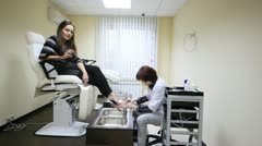 Client sits in armchair for pedicure and cosmetician does to she pedicure Stock Footage