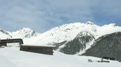 Chalets stand on slope of mountain against mountains and are covered by snow Stock Footage