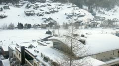 Cottages and hotels of Soelden are visible below in valley from rope-way - stock footage