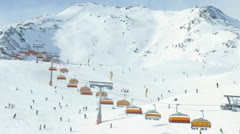 Rope-way with orange seats does descent and rise of skiers Stock Footage
