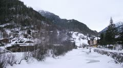 Near to hotels and houses in valley there is river Stock Footage