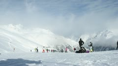 Skiers go down from mountain against clouds and blue sky Stock Footage