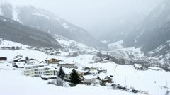 In valley where there are hotels and skiers it is snowing Stock Footage