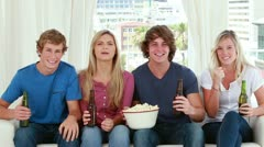 Happy friends eating popcorn while sitting Stock Footage