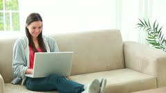 Smiling brunette woman using her personal computer Stock Footage