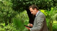 Businessman working on tablet computer in the park, steadicam shot Stock Footage