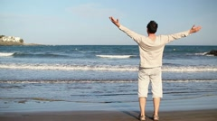 Man walk on beach and raising hands to the sky, slow motion HD Stock Footage