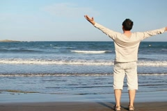 Man walk on beach and raising hands to the sky, slow motion NTSC Stock Footage