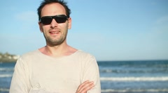 Happy man by the sea looking to camera HD Stock Footage