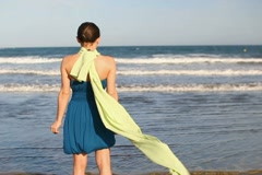 Woman in blue dress and sarong standing by the sea, slow motion NTSC Stock Footage