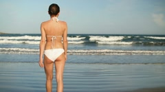 Sexy woman in bikini walk and stand on beach, slow motion HD Stock Footage