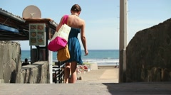 Woman in blue dress with summer bag walking to the beach HD Stock Footage