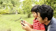 Stock Video Footage of Father and Son Playing with Helicopter Together