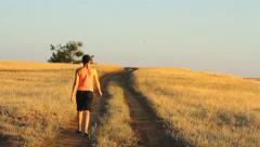 Girl walking on empty rural road far away in summer day - stock footage