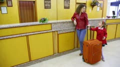 Mother and her daughter stand with trunk at hotel reception Stock Footage