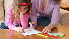 Mother with daughter sit on sofa at wooden table and draw with markers Stock Footage