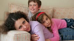 Mother and her kids boy and little girl lay on sofa Stock Footage