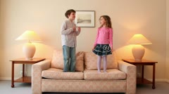 Two kids jump on sofa and then run away from room with lamps on each side - stock footage