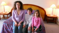Mother and her kids boy and girl sit on sofa and clap hands when watch tv Stock Footage
