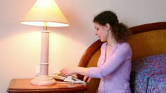 Woman enters number and talks phone in room with lamp near bed Stock Footage