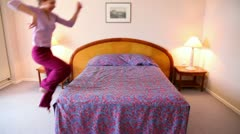 Young woman runs and jumps on bed then lies on it Stock Footage
