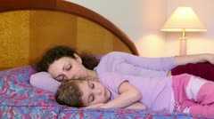 Mother and daughter lay on bed, mom sleeps but girl does not Stock Footage