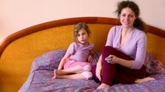 Mother and daughter sit on bed and watch tv with remote control Stock Footage