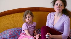 Mother and her little daughter sit on bed and watch tv Stock Footage