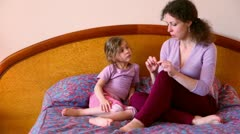 Mother sits on bed with her little daughter and tells her about something Stock Footage