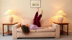Young woman lies on sofa and shake legs at room with lamps on each side Stock Footage