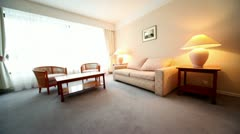 Room with lamps on each side of bed and pair of armchairs at table Stock Footage