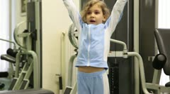 Little girl exercises with dumbbells at background of training equipment Stock Footage