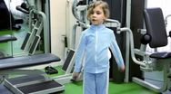 Little girl exercises with dumbbells at background of training equipment near Stock Footage