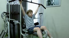 Little boy sits and hauls light weight on training equipment Stock Footage