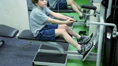 Little boy sits on bench and hauls weight on training equipment Stock Footage