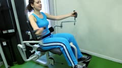 Young woman sits and exercises on training equipment - stock footage