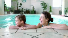 Little girl with her mother stay on edge of indoor pool Stock Footage
