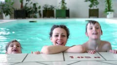 Mother with two kids boy and girl smile at pool edge Stock Footage