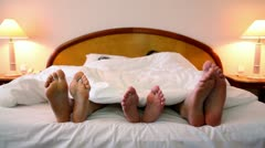 Parents with their son lay in bed under blanket and move bootless feet Stock Footage
