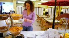 Woman takes cereal and puts it to plate at breakfast time in cafe Stock Footage