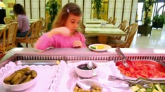 Little girl takes cucumber and puts it to plate in cafe Stock Footage