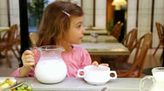 Little girl takes jug with milk and pours it in plate at restaurant Stock Footage