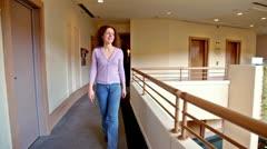Young woman walks along corridor in multiple floor building Stock Footage
