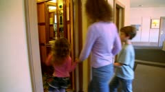 Stock Video Footage of Mother with two kids walk in elevator, then doors closes