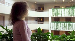 Woman stand at balcony with plants in multiple floor building Stock Footage