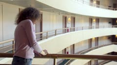 Woman stand at balcony with handrail in multiple floor building Stock Footage