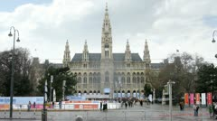 Tourists walk in front of Rathaus near road where go cars and trams Stock Footage